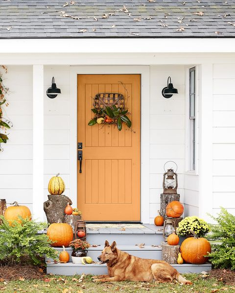 tobacco basket wreath on an orange door with loads of pumpkins on the porch and stairs