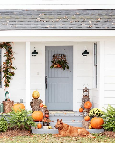 fall door with tobacco basket werath and lots of orange pumpkins and vintage lanterns