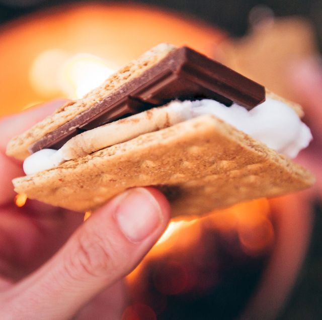 hand holding s'more over fire pit