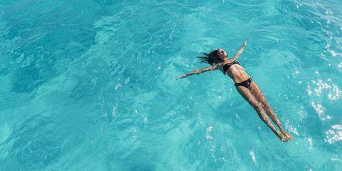 Vrouw ligt in een zwembad met armen wijd