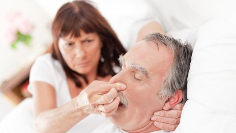 vrouw knijpt neus van snurkende man dicht