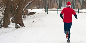 Guy Running in Snow with Santa Hat