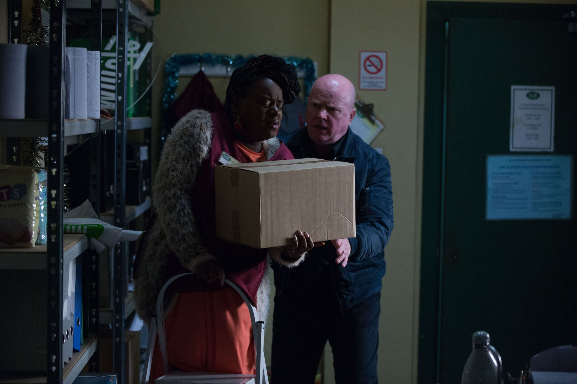 Phil Mitchell helps Kim Fox at the Minute Mart in EastEnders