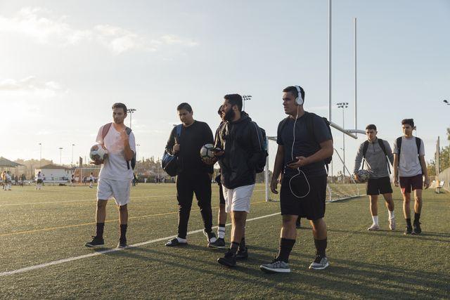 varios jugadores de fútbol se retiran del campo con el balón en la mano tras un partido