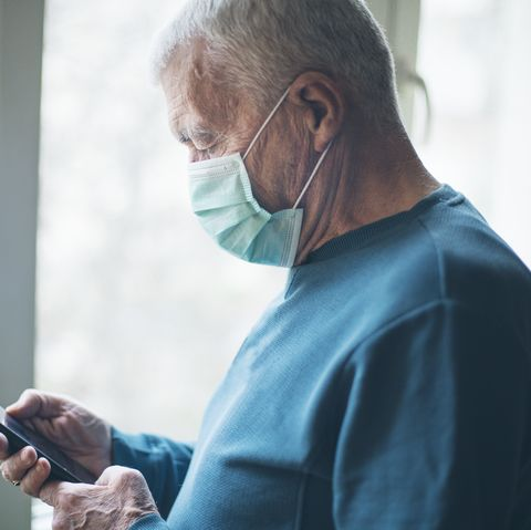 senior man wearing a protective mask and using a phone at home, during covid 19 pandemic