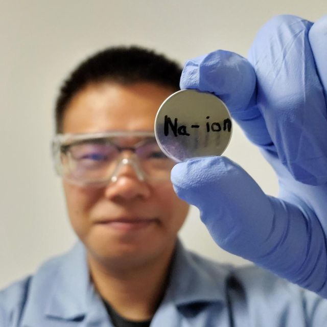 researcher junhua song, smiling, holding up a sodium ion disk
