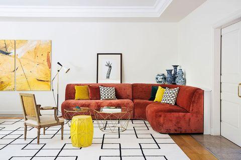 sofá en terciopelo teja contrastado con elementos mostaza