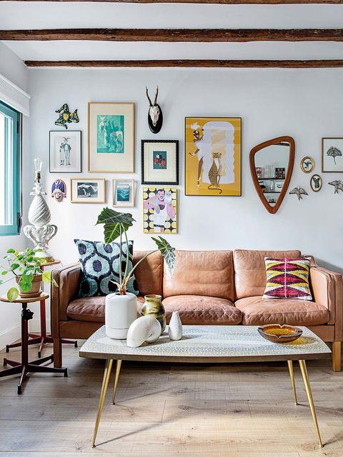 un sofá de piel es el centro de este salón que combina cuadros y objetos decorativos en su pared