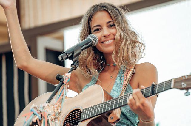 sofia ellar en concierto con su gitarra mirando a cámara con el pelo suelto y un top azul