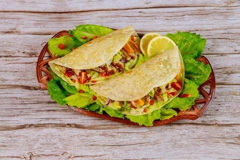 Soft flour tortillas stuffed with lettuce, meat and cheese on wooden background.