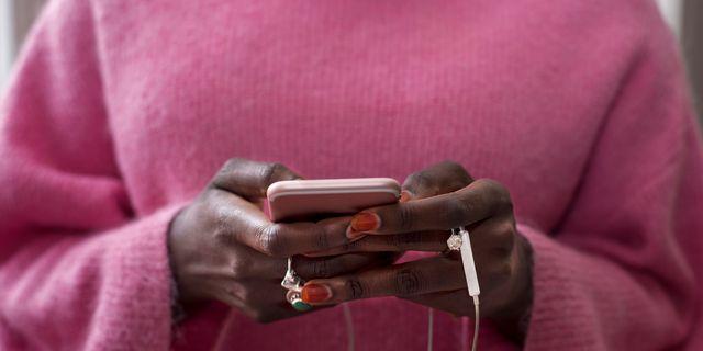 vrouw in roze trui met telefoon in hand