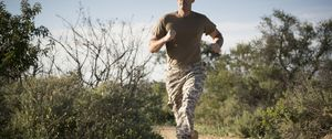 Soldier wearing combat clothing running, Runyon Canyon, Los Angeles, California, USA