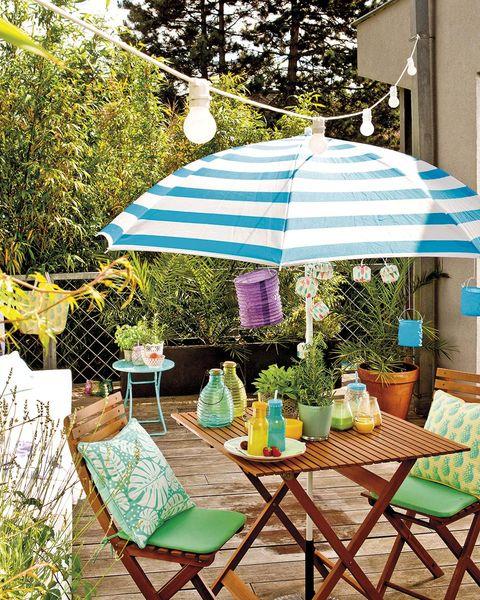comedor en el jardín con sombrilla de rayas azules