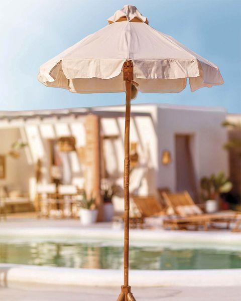 sombrilla de madera y tela blanca en la zona de piscina