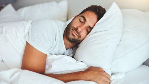 man in een wit t shirt ligt op bed