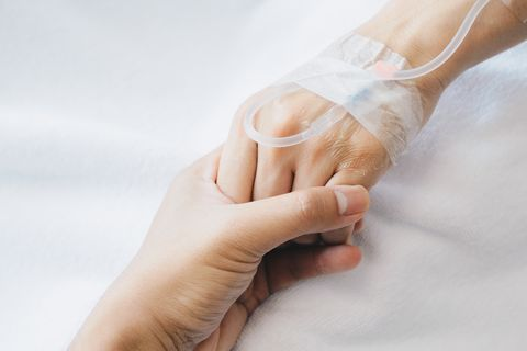 someone hand holding patient hand during receiving intravenous fluid directly into a vein