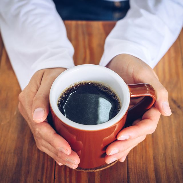 someone hands holding a mug of black coffee before drinking