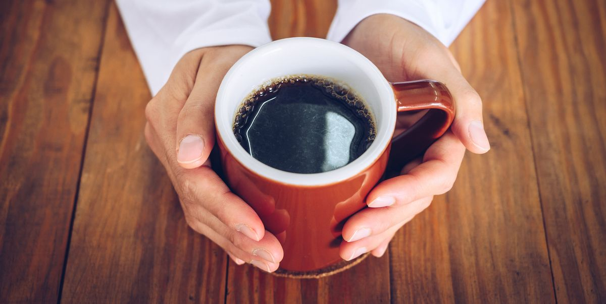 someone hands holding a mug of black coffee before royalty free image 1610127377 ?crop=1 00xw:0 739xh;0,0 261xh&resize=1200:*.