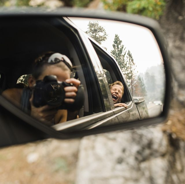 son screaming while mother photographing with camera reflecting on side view mirror
