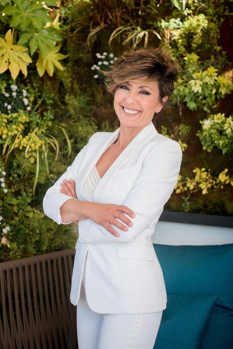 la presentadora de 'ya es mediodía' sonríe con un traje blanco en un jardín