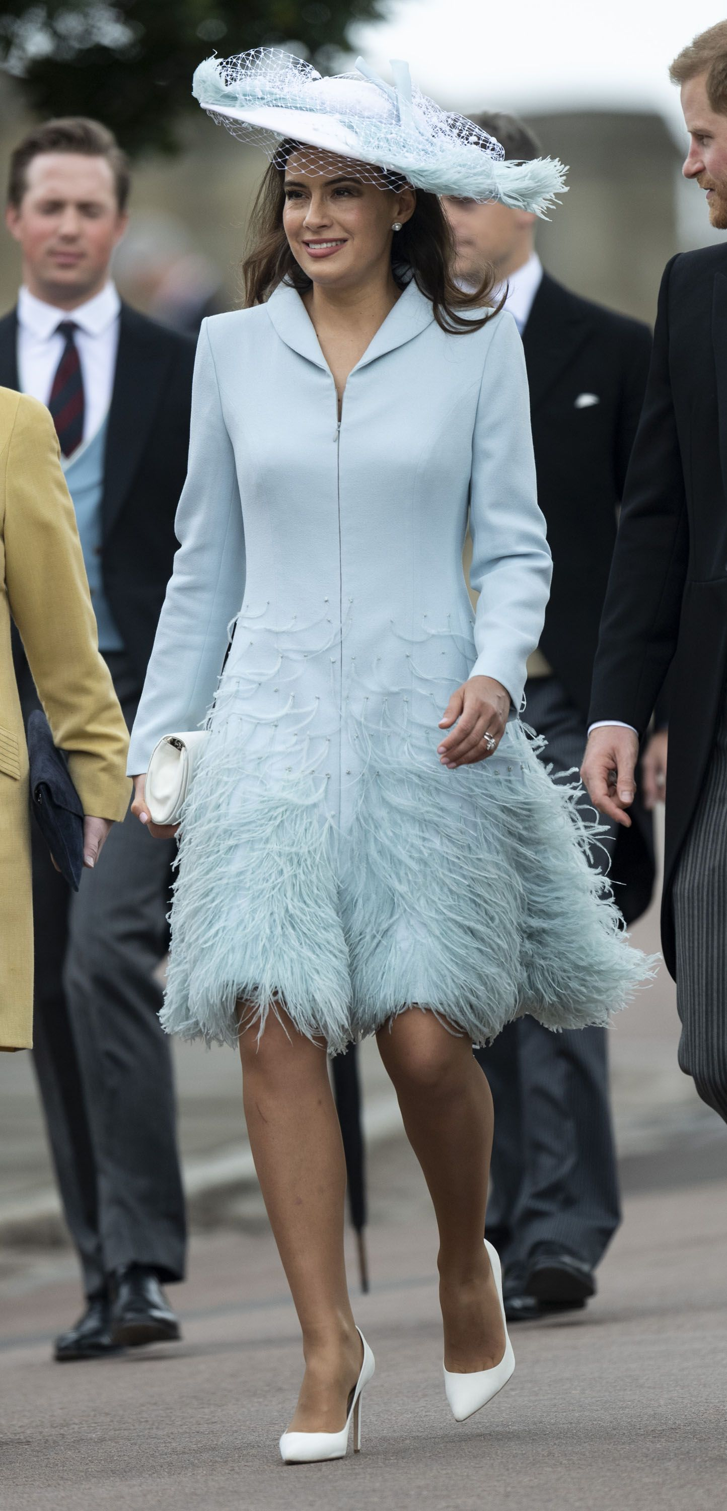 In a soft blue feathered ensemble and matching hat.