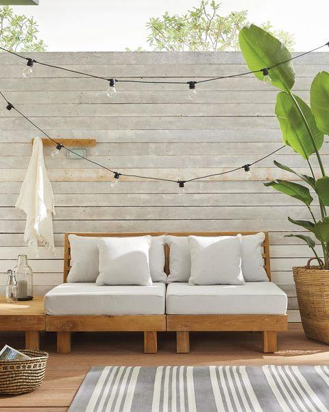 terrazas y jardines porche moderno con sofá y guirnalda de luces