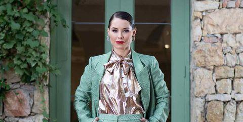La cantante luce un traje verde de By Malene Birger By Zalando; camisa con lazo dorada de Cézane; botines con puntera metálica de Exé Shoes; y pendientes de Patricia Nicolas.