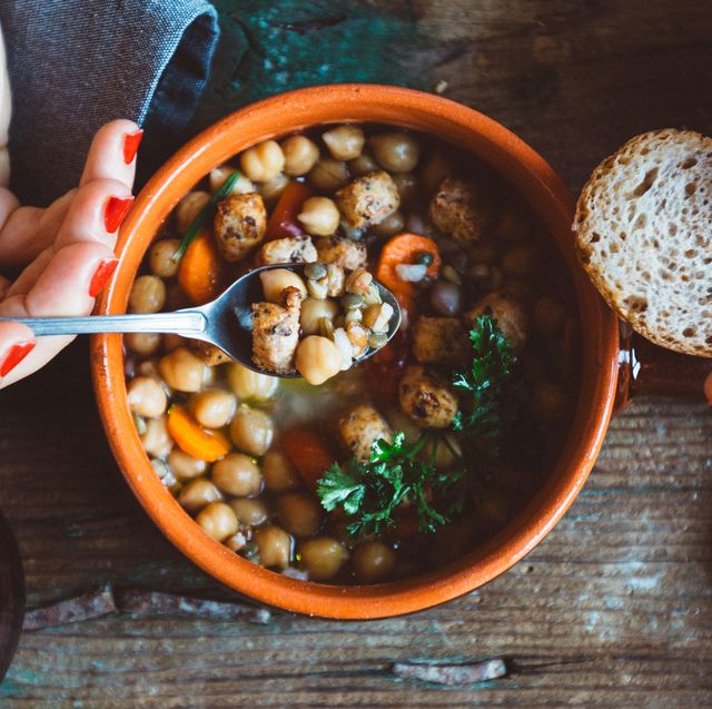 woman eating hearty soup in orange bowl with bread