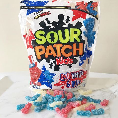 a bag of sour patch kids red, white  blue variety with candies spread on the table