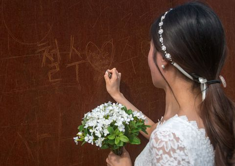south korean woman called juyeon writing a peace message on the north and south korea border, sudogwon, paju, south korea