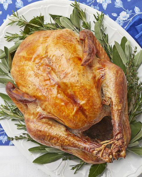 roasted thanksgiving turkey on white platter with herbs