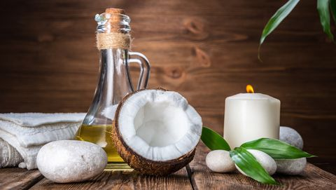 spa still life with coconut, massage oil and candle on a wooden background