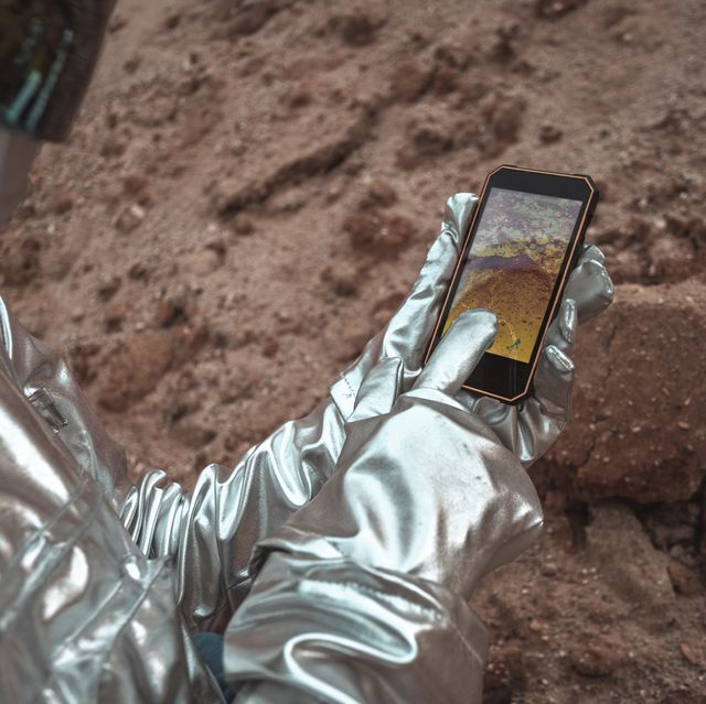 Spaceman examining new planet, using smartphone
