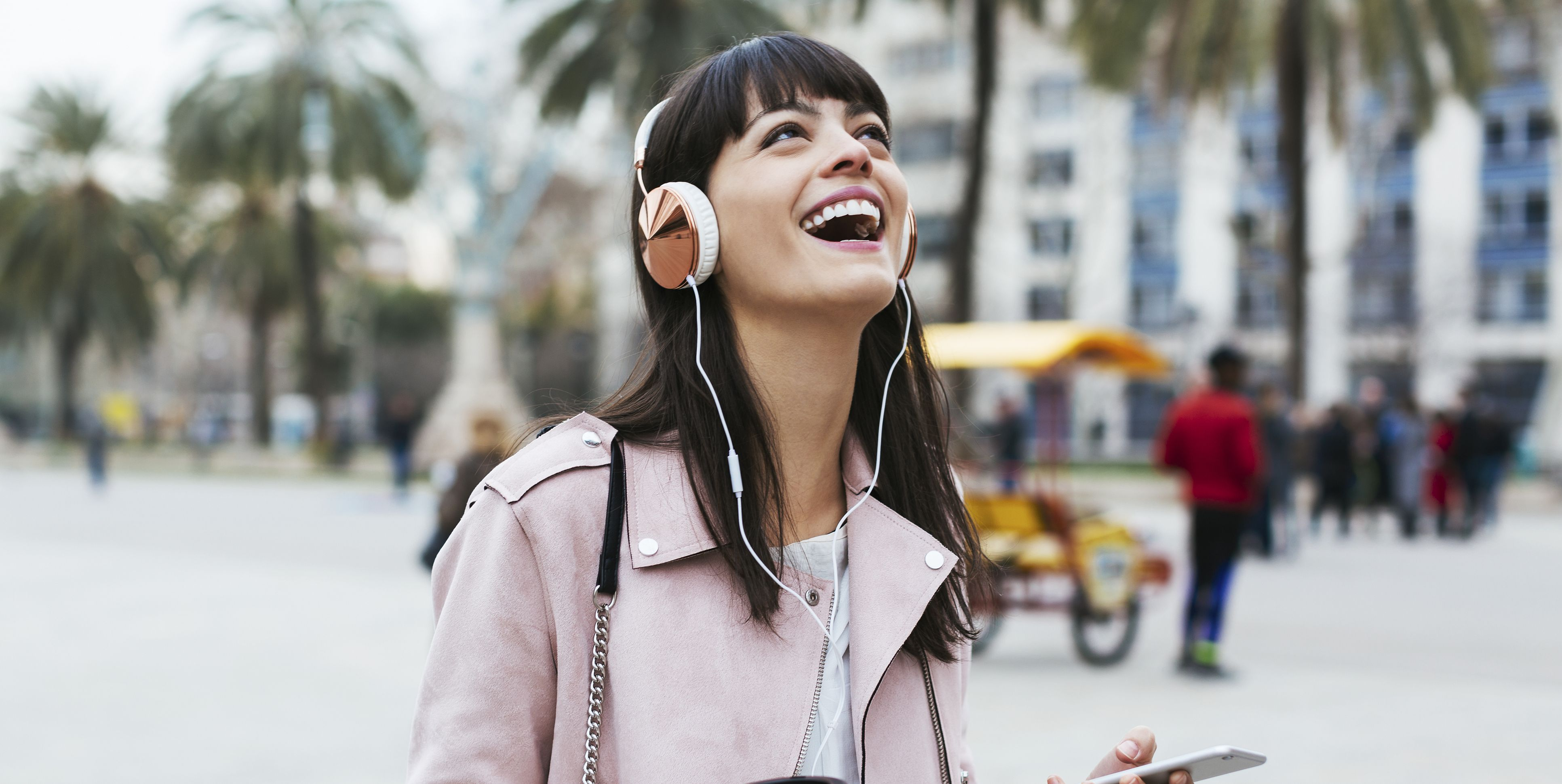 Spain, Barcelona, laughing woman with coffee, cell phone and headphones in the city
