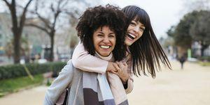 Spain, Barcelona, portrait of two exuberant women in city park