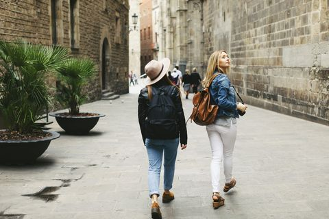 Spain, Barcelona, two young women walking in the city