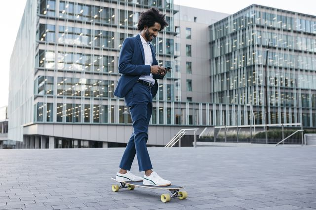 spain, barcelona, young businessman riding skateboard and using cell phone in the city