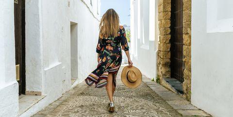 spain, cadiz, vejer de la frontera, back view of fashionable woman walking through passage