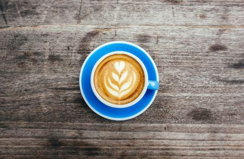 foamy coffee latte with design in blue mug