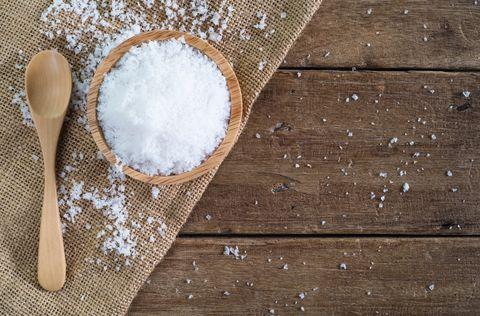 sale marino bianco in una ciotola di legno con un cucchiaio di legno