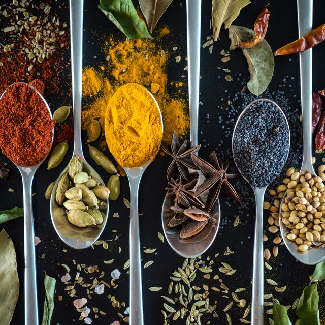 spices on spoon against black background