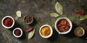 Spices seasoning and herbs variety in ceramic bowls. Different ground peppers, chili pepper, turmeric, bay leaf, cinnamon over dark metal background. Flat lay, space. Cooking concept