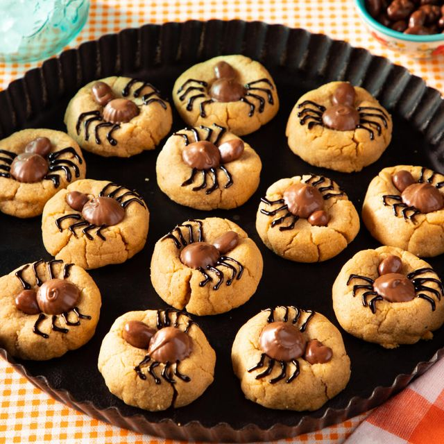 peanut butter cookies topped with candies and icing to look like spiders