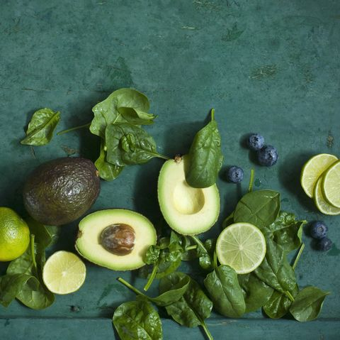 spinach leaves, avocados and blueberries on green ground