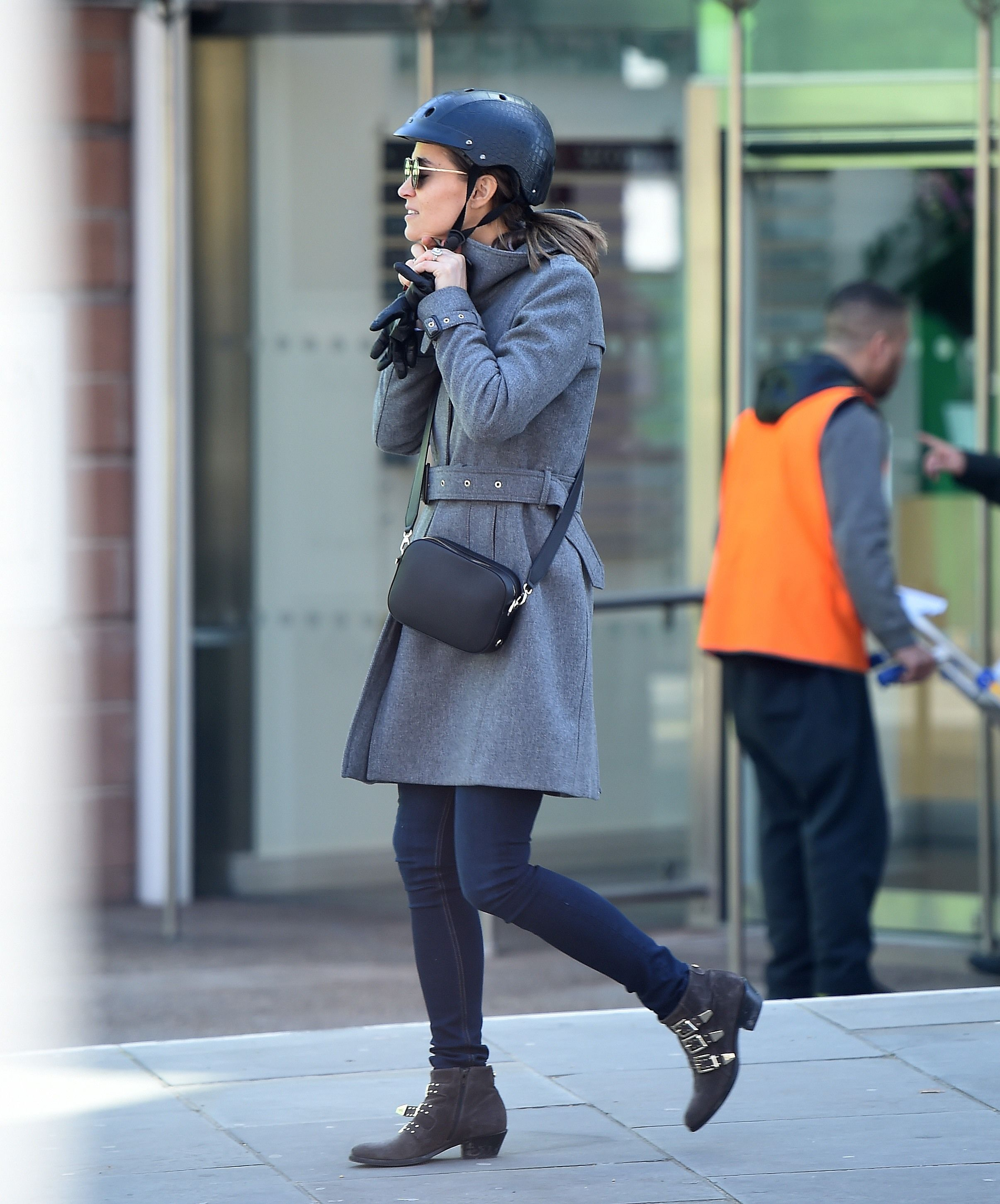 Pippa rode around the Chelsea neighborhood in London while wearing a gray belted trench coat, blue jeans, and a pair of Russell & Bromley boots . She kept all her belongings in her trusty Pop and Suki camera bag.