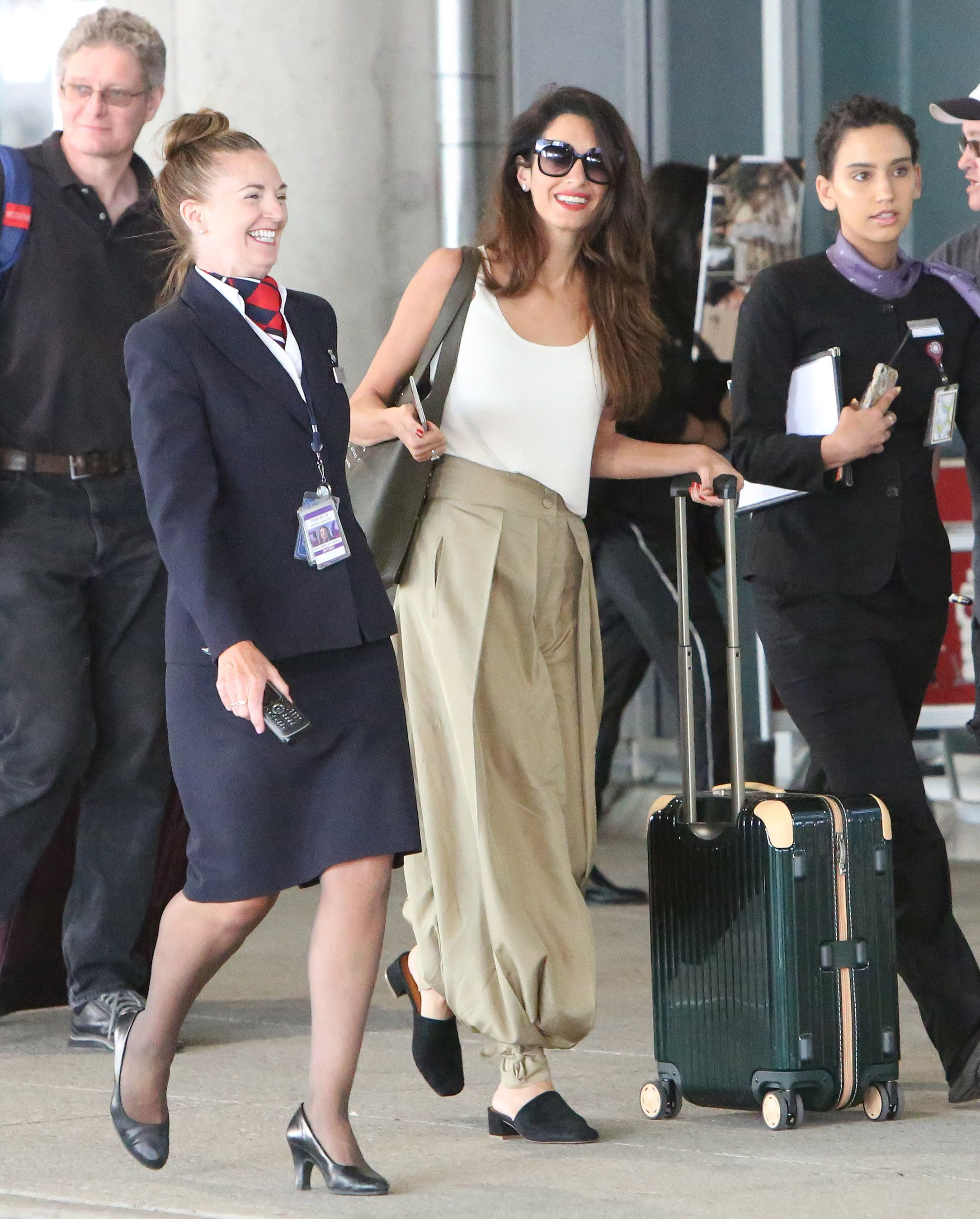 June 21, 2018 In a white tank, beige ankle-tie harem pants, and black suede mules at the Toronto airport.