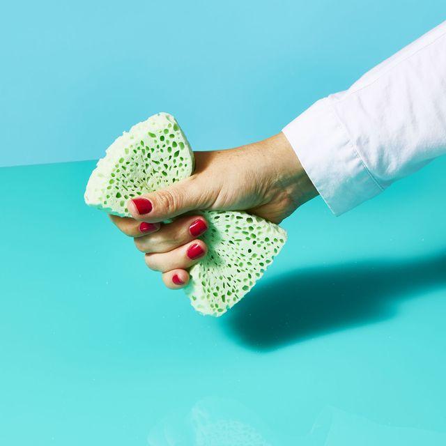 hand holding sponge, washing dishes