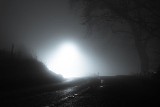 a spooky, eerie country road passing through a hill, with a light in the distance, on a mysterious foggy, winters night