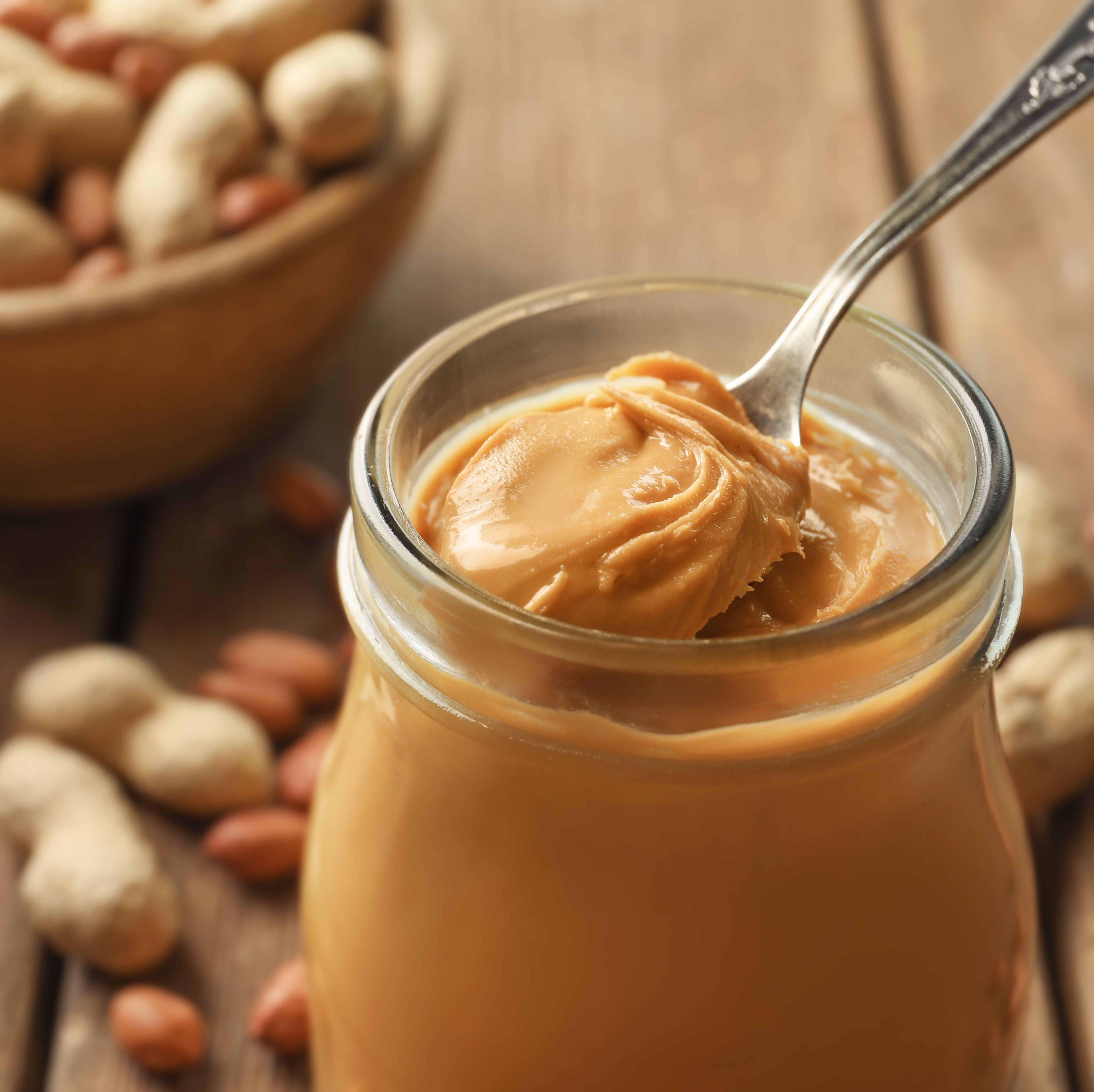 Spoon and glass jar with creamy peanut butter on kitchen table, closeup