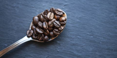 spoon with roasted coffee beans